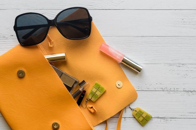 Fashion-konzept. weibliche kosmetikprodukte, sonnenbrille, ohrringe und orangefarbene handtasche.