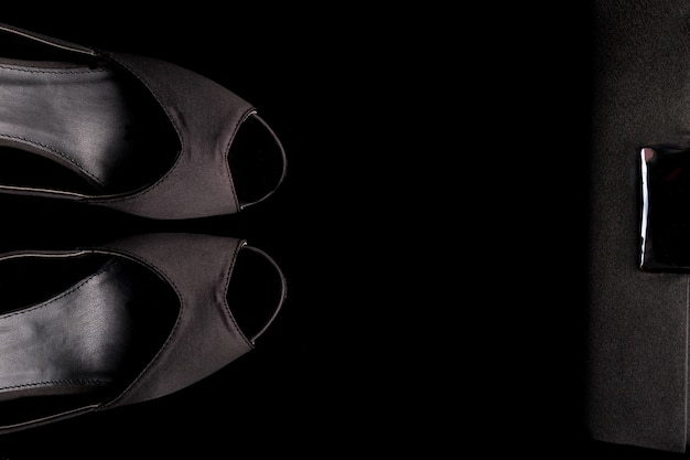 Fashion lady zubehör set. minimal. schwarze schuhe und tasche auf schwarz. flach liegen.