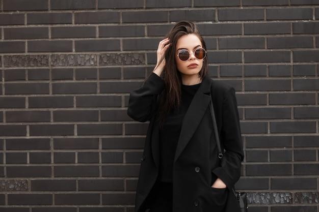 Fashion model wunderschöne junge frau in cooler runder sonnenbrille in modischer schwarzer freizeitjacke in stylischem t-shirt in der nähe moderner backsteinmauer in der stadt. amerikanisches sexy mädchen im trendigen jugendoutfit in der straße.