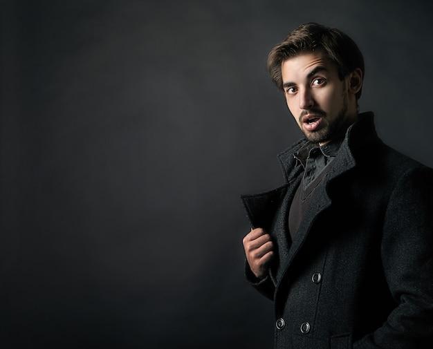 Fashion shot eines jungen gutaussehenden mannes im mantel auf schwarzem hintergrund
