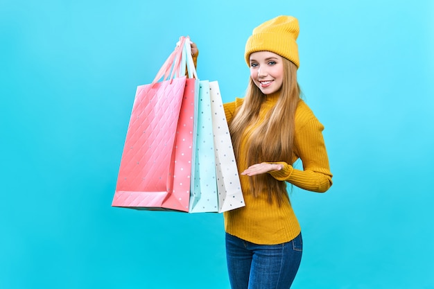 Fashionista mädchen mit taschen. junge glückliche frau mit einkäufen. freudige schönheit wurde zum verkauf angeboten, auf blauem grund.
