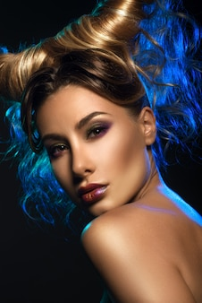 Fashionrt-porträt der sexy schönheit mit hörnern über dunkelheit