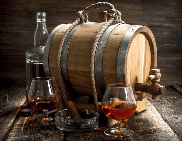 Fass mit französischem cognac, gläsern und einer zigarre. auf einem hölzernen hintergrund.
