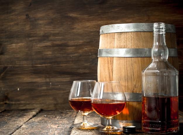 Fass mit gläsern french cognac. auf einem hölzernen hintergrund.