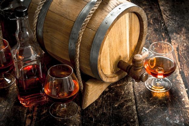 Fass mit langem cognac und brille. auf einem hölzernen hintergrund.