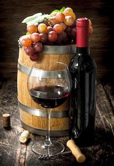 Fass rotwein mit trauben und korkenzieher. auf einem hölzernen hintergrund.