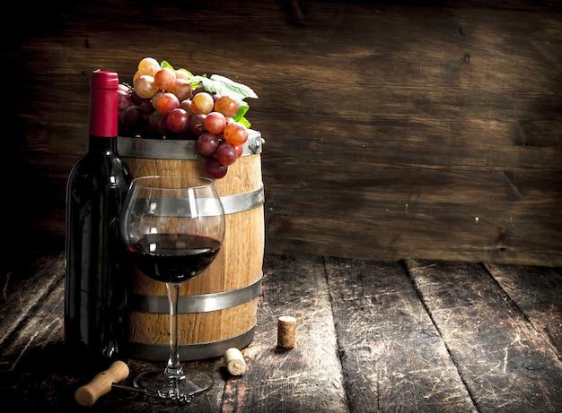 Fass rotwein mit trauben und korkenzieher. auf einem holztisch.