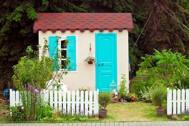 Fassade des kleinen hauses mit aquafenster und -tür, topfblumen an der wand und blick auf den garten