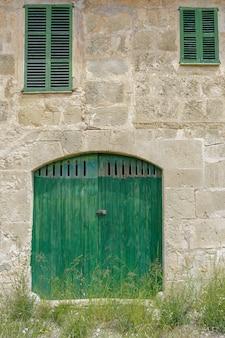 Fassade eines alten bauernhofes. türen und fenster in naturholzstruktur, steinmauern von mares, typisch für mallorca, landhaus für agrotourismus, verschiedene fenster, landhaus.