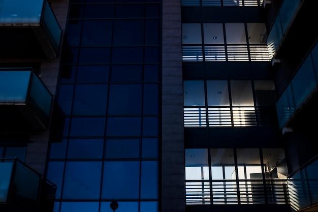 Fassade eines modernen verglasten gebäudes, in dem arbeiter internationale geschäfte auf einem globalen markt abwickeln.