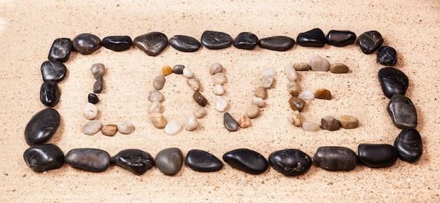 Fassen sie die liebe ab, die mit kieseln auf den sand eines strandes geschrieben wird