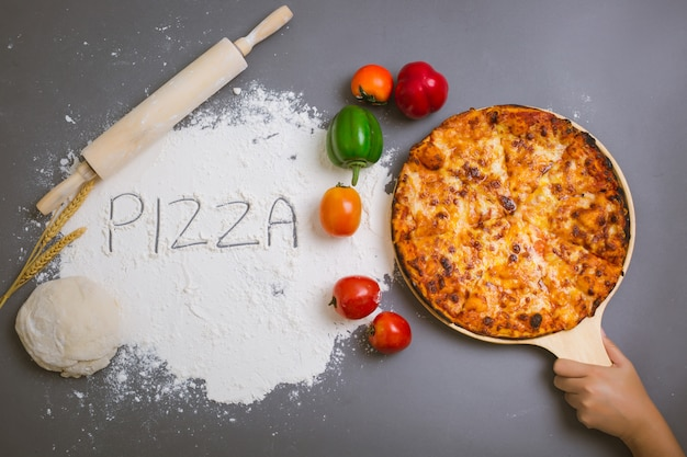 Fassen sie die pizza ab, die auf mehl mit einer geschmackvollen pizza geschrieben wird
