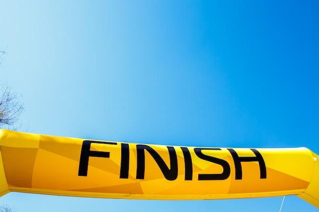 Fassen sie ende auf einer gelben fahne gegen einen blauen himmel ab.