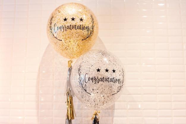 Fassen sie glückwunsch auf fliesen-wandhintergrund der ballone weißem ab