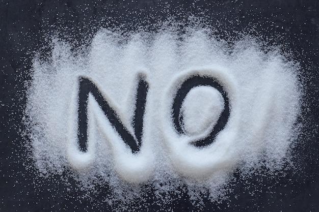 Fassen sie no ab, das in einen stapel des weißen granulierten zuckers geschrieben wird