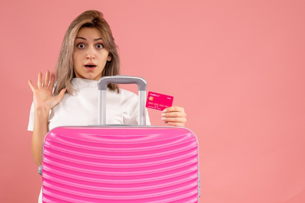 Fassungslose junge frau mit rosa koffer mit karte