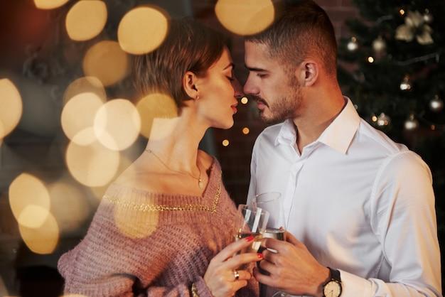 Fast der kuss. nette paare, die zuhause neues jahr mit klassischer schöner kleidung auf ihnen feiern