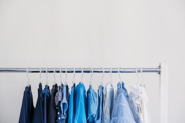 Fast fashion nachhaltige mode minimalistische garderobe auswahl an weiblicher blauer kleidung zum aufhängen