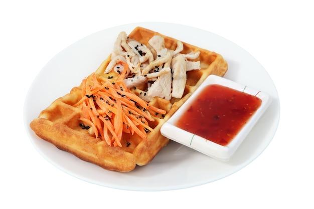 Fast food auf dem teller, belgische waffel, ein salat der geriebenen karotte, scheiben der hühnerbrust, schüssel der roten soße, isoliertes bild auf weißem hintergrund.