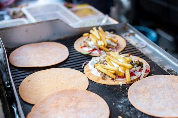 Fast food auf der straße. ein köstliches gericht aus fleisch und soße mit kartoffeln und gemüse auf einem brotkuchen.