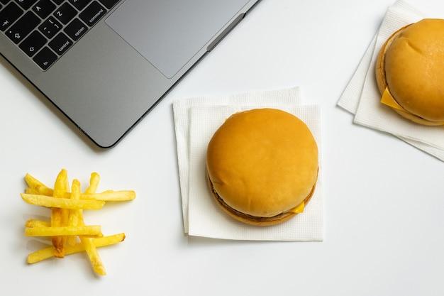 Fast food bei der arbeit snacks. laptop, hamburger und pommes frites am arbeitsplatz.