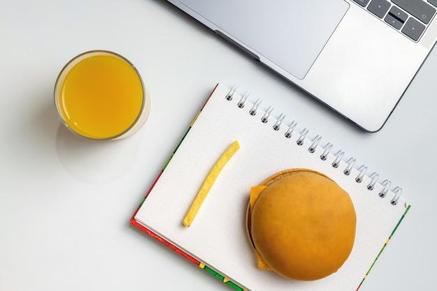 Fast food bei der arbeit snacks. laptop, notizbuch, hamburger und pommes-frites am arbeitsplatz.