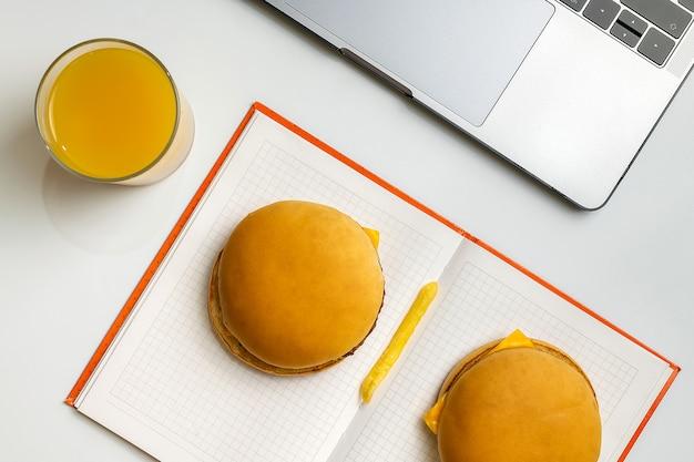 Fast food bei der arbeit snacks. laptop, notizbuch, zwei hamburger und pommes-frites am arbeitsplatz.