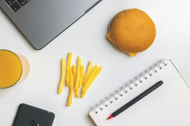 Fast food bei der arbeit snacks. laptop, telefon, hamburger und pommes frites am arbeitsplatz.