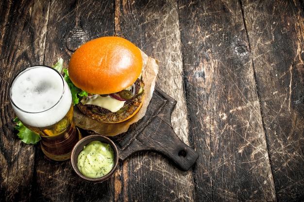 Fast food. ein großer burger mit rindfleisch und einem glas bier. auf einem hölzernen hintergrund.