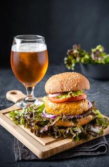 Fast food. ein großer burger und ein glas bier. auf einem dunklen hintergrund.
