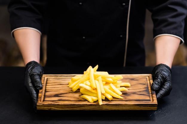 Fast-food-gericht. abgeschnittene aufnahme des kochs, der gesalzene pommes frites auf rustikalem holzbrett hält.