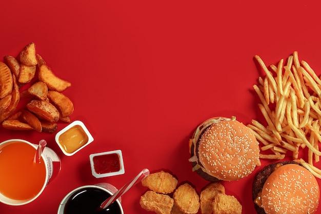 Fast-food-gericht draufsicht fleisch burger kartoffelchips und glas getränk auf rotem hintergrund zum mitnehmen kompo...