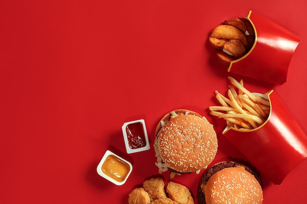 Fast-food-gericht draufsicht fleisch burger kartoffelchips und nuggets auf rotem hintergrund zusammensetzung zum mitnehmen