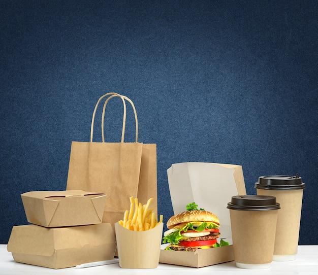 Fast food großes mittagessen set aus leckeren hamburger pommes frites papier kaffeetassen braune papiertüte und box