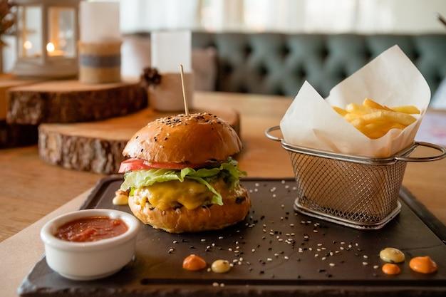 Fast food. hamburger. frische leckere leckere hausgemachte burger. dieser hamburger mit rustikalem holztisch der pommes-frites. fast-food-konzept bild. steakhaus oder schnellrestaurantkonzeptbild