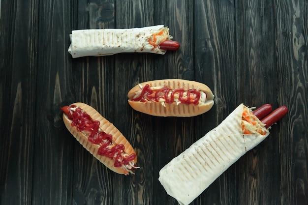 Fast food.hot dog mit würziger sauce und shawarma auf dunklem hintergrund.