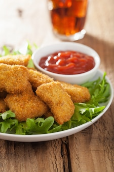 Fast-food-hühnernuggets mit ketchup, cola
