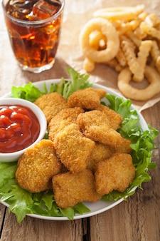 Fast-food-hühnernuggets mit ketchup, pommes frites, cola