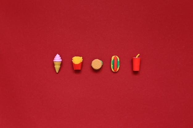 Fast food liegt auf einem roten hintergrund. essen im hintergrund. hochwertiges foto