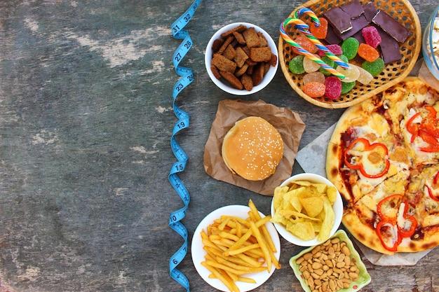 Fast food, maßband auf altem holztisch. konzept des junk-essens. draufsicht. flach liegen.