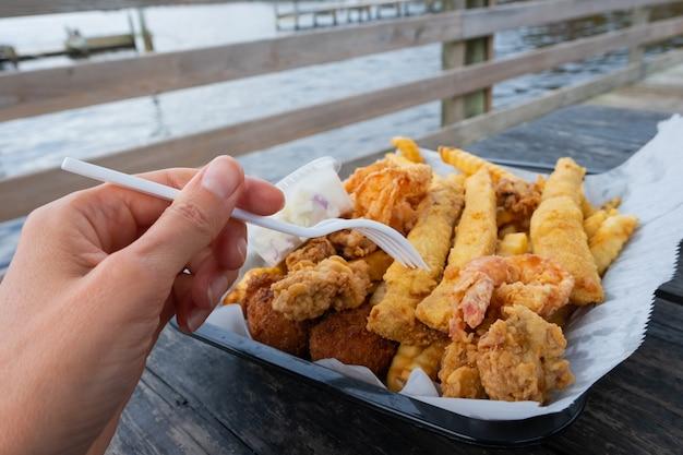 Fast food meeresfrüchte. knuspriger fisch, garnelen und pommes. gebratene meeresfrüchte, pommes frites, zitronenscheiben in einweggerichten in einem restaurant im hafen.