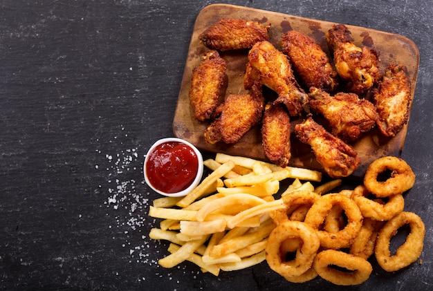Fast-food-produkte: zwiebelringe, pommes frites und brathähnchen auf dunklem tisch, draufsicht