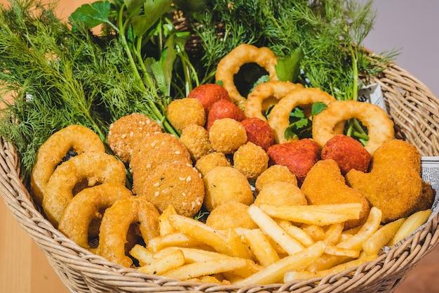 Fast-food-snackkorb mit zwiebelringen und falafel - nahaufnahme mit petersilie und dills