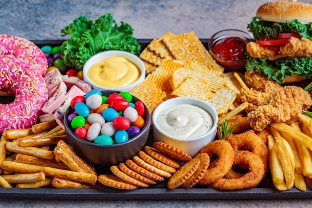 Fast-food-sortiment. junk-food-konzept. ungesunde nahrung für herz, zähne, haut, figur.