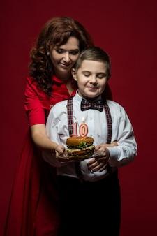 Fast-food-tag, hamburger-tag, burger-tag. nahaufnahmeporträt von mutter und sohn mit fast food in ihren händen