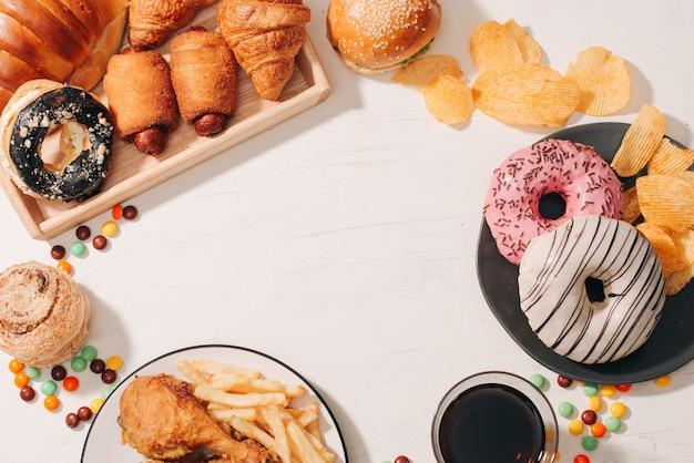 Fast food und ungesundes esskonzept - nahaufnahme von fastfood-snacks und cola-getränken auf weißem tisch
