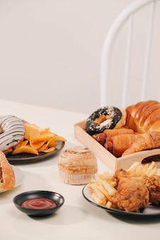 Fast food und ungesundes esskonzept - nahaufnahme von hamburger oder cheeseburger, frittierten tintenfischringen, pommes frites, getränk und ketchup auf holztisch
