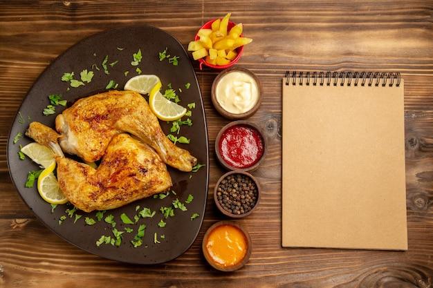 Fast food von oben in den tellerschüsseln mit schwarzen pfeffersaucen und pommes frites zwischen dem teller mit hähnchenschenkeln und sahnenotizbuch