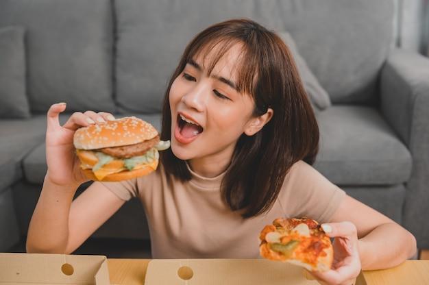Fast food zum mitnehmen nach hause. burger essen beim mitnehmen und liefern. asiatischer frauenlebensstil im wohnzimmer. soziale distanzierung und neue normalität.