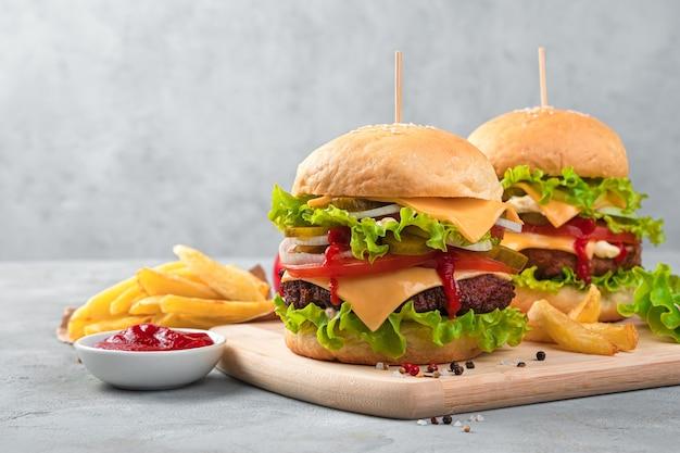 Fast food, zwei große burger, sauce und pommes frites an einer grauen wand. seitenansicht, kopienraum.